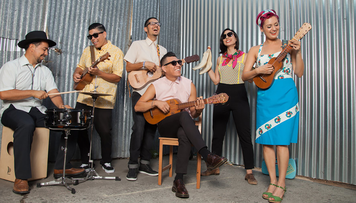 Las Cafeteras plays in front of a metal wall.