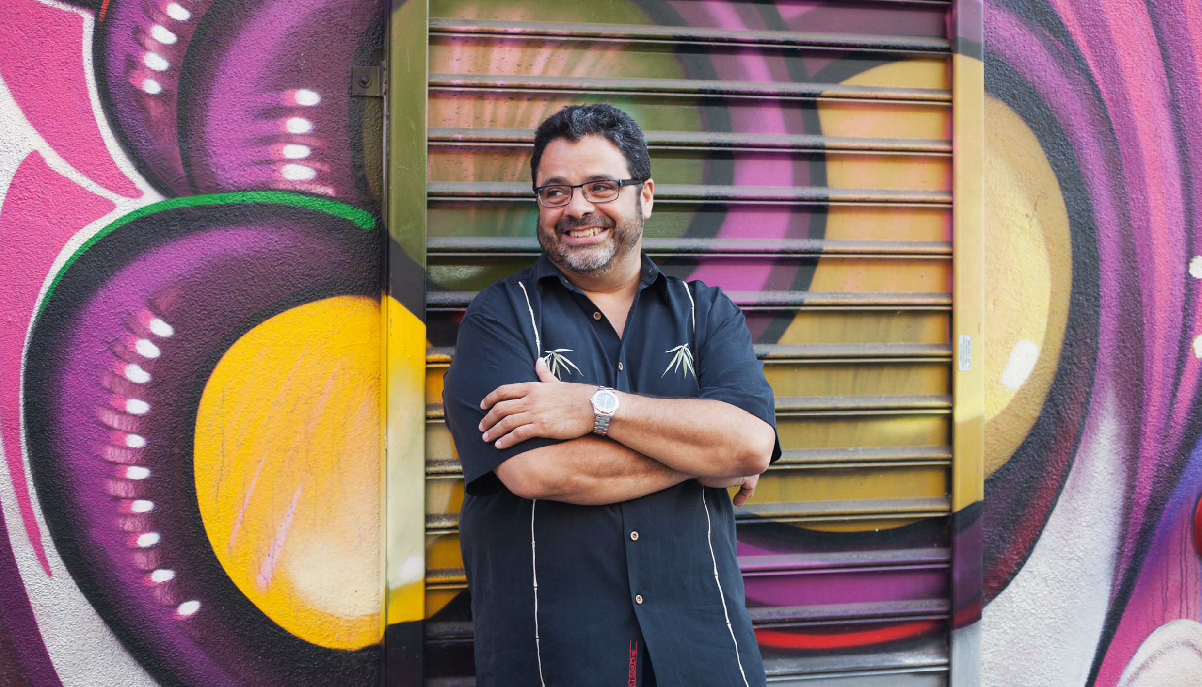 Arturo OFarrill leans against a colorful mural. Photo by Laura Mariet.