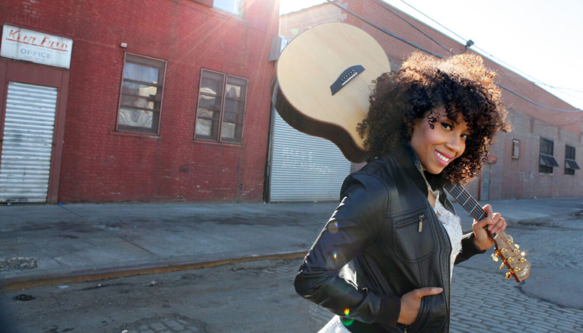 Rissi Palmer walking across the street with her guitar over her shoulder. Photo by Jimmy Bruch.
