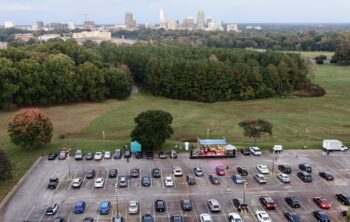 Ariel photograph of NC State LIVE at the Lot concert with Rissi Palmer. Cars in parking lot in front of stage. Raleigh skyline in distance.