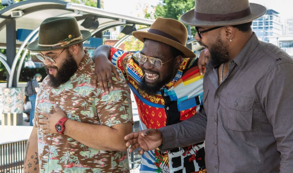 The three members of The Hamiltones walk down the street laughing. Photo by Alex Cason.