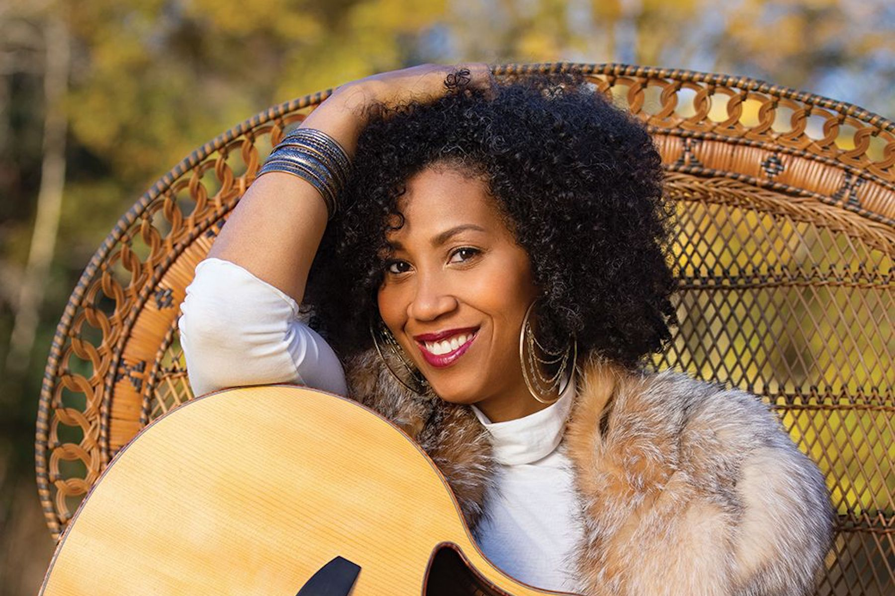 Rissi Palmer sits in a wicker chair holding her guitar. Photo by Samantha Everette.